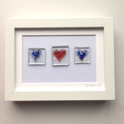 Hand made glass blue hearts in glass with a single re heart in glass